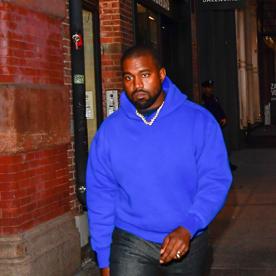 Kanye West in a blue Yeezy Gap hoodie